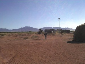 A desert landscape with a man standing in the center, with a green tent and communications antennas visible in the background.